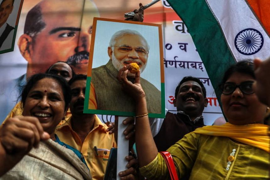 Indian Bharatiya Janata Party (BJP) supporters hold the national flag and poster of Indian Prime Minister Narendra Modi, shout slogans and distribute sweets as they celebrate the removal of Article 370, in Mumbai, India on Aug 6, 2019.