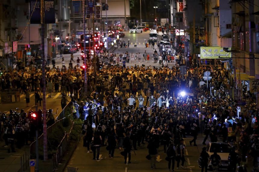 Residents and protesters face riot police after they gathered to demand the release of a student leader outside a police station at Sham Shui Po district in Hong Kong on Aug 7, 2019.