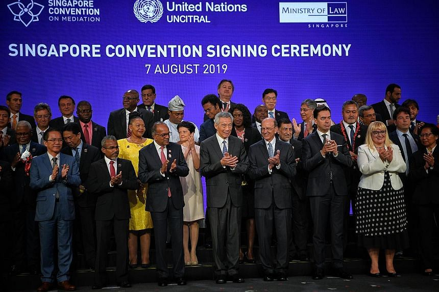 Prime Minister Lee Hsien Loong, flanked by Law and Home Affairs Minister K. Shanmugam and UN Assistant Secretary-General for Legal Affairs Stephen Mathias, with signatories and heads of delegations after the signing of the Singapore Convention on Med