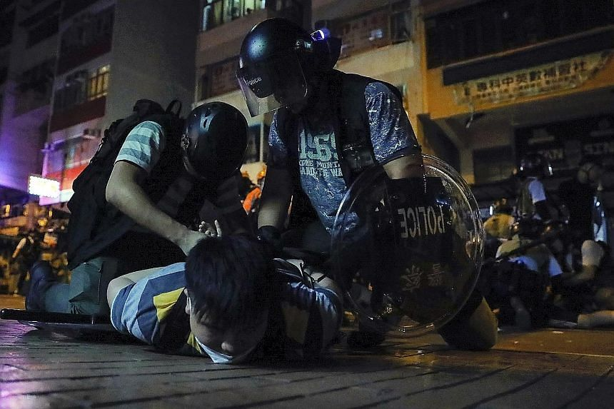 Above: Lawyers on their silent march in Hong Kong yesterday. Left: A protester being arrested in Sham Shui Po district, where a group of demonstrators laid siege to a police station on Tuesday after the arrest of a student leader. PHOTOS: ASSOCIATED