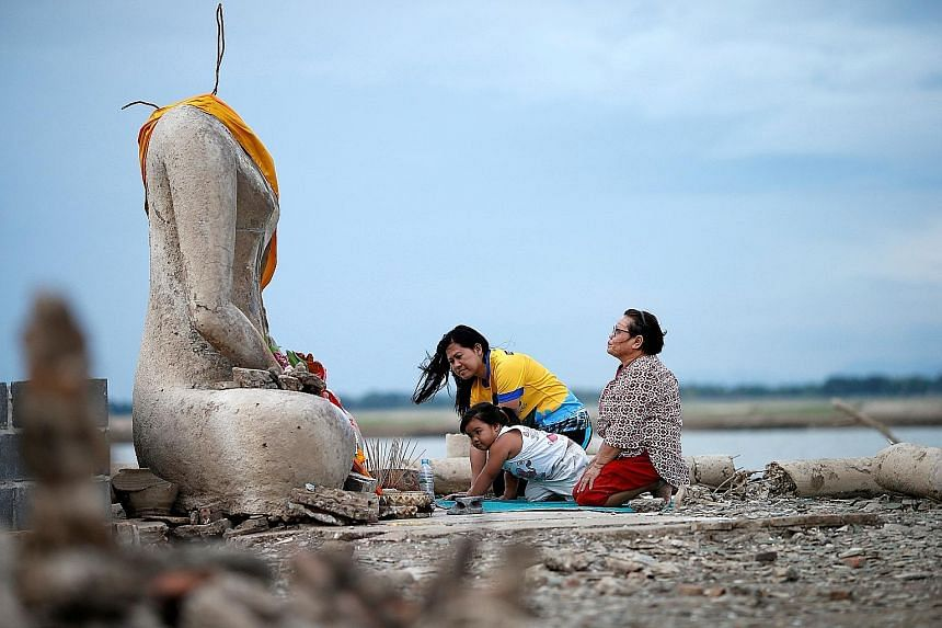 Visitors exploring the ruins of Wat Nong Bua Yai (right), while a family prays at the headless Buddha statue (below). Construction of a dam 20 years ago caused the temple to be submerged, but drought has caused water levels in the reservoir to fall t