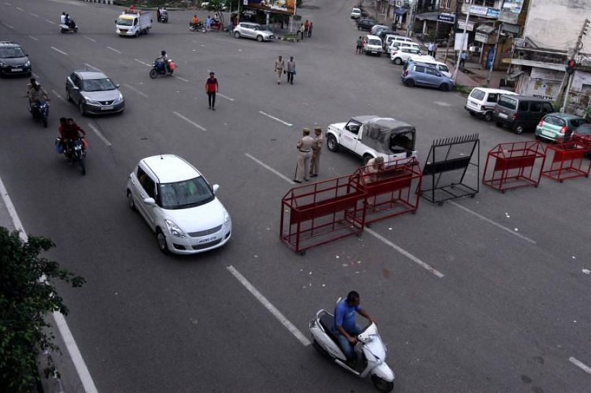 Vehicles move past a police checkpoint in Jammu, on Aug 8, 2019, as some restrictions on movement remained in place in the city following the Indian government's controversial move to strip Jammu and Kashmir of its autonomy.