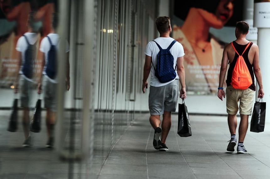 Two male shoppers with shopping bags along Orchard Road.