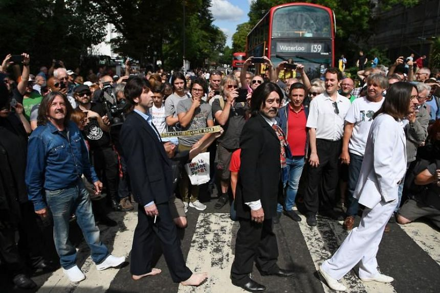 Fans mobbed the pedestrian crossing exactly five decades on from the moment when Britain's legendary Fab Four walked across.