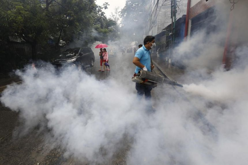 A sanitation inspector uses a fogging machine during a fumigation operation against the spread of Dengue in a community of Marikina City, east of Manila, on Aug 8, 2019.