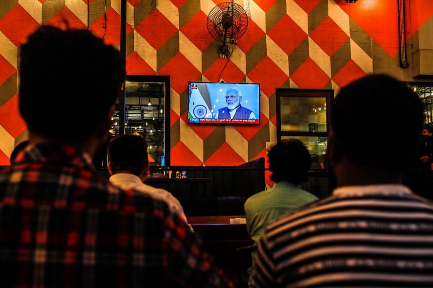 People watch a live address by Indian Prime Minister Narendra Modi.