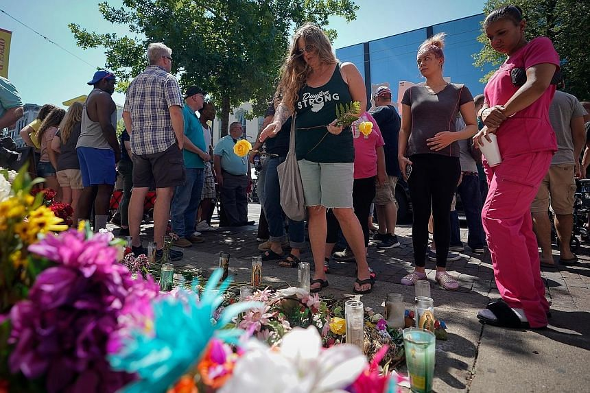 Mourners gathering on Wednesday at the site of Sunday morning's mass shooting, where nine people and the suspect were killed, in Dayton, Ohio.