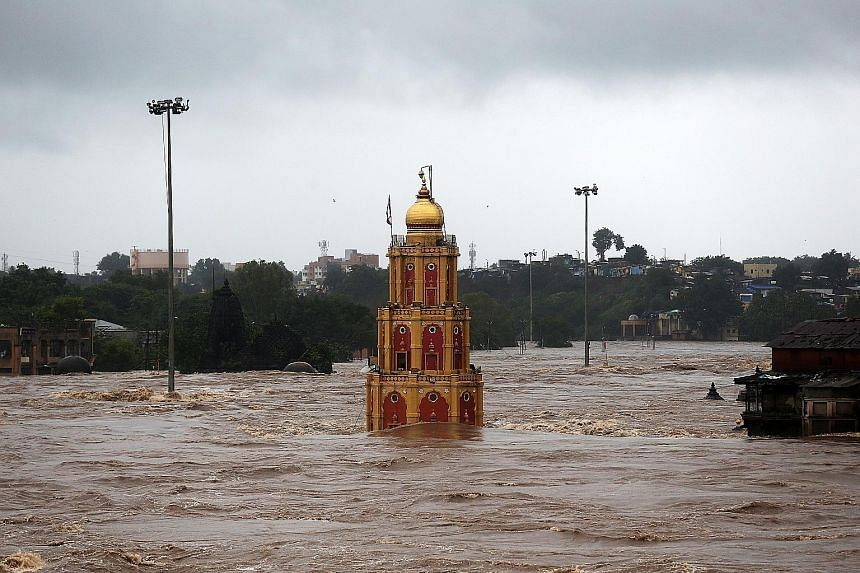 A temple partially submerged in the waters of the overflowing Godavari River following heavy rain in Nashik city in India's Maharashtra state, where the death toll from the floods hit 25.