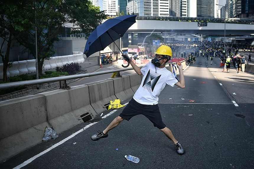 A protester, armed with an umbrella as a shield, throwing an egg at the police outside the Legislative Council in Hong Kong on Monday. More protests are planned in several districts across the city this weekend.
