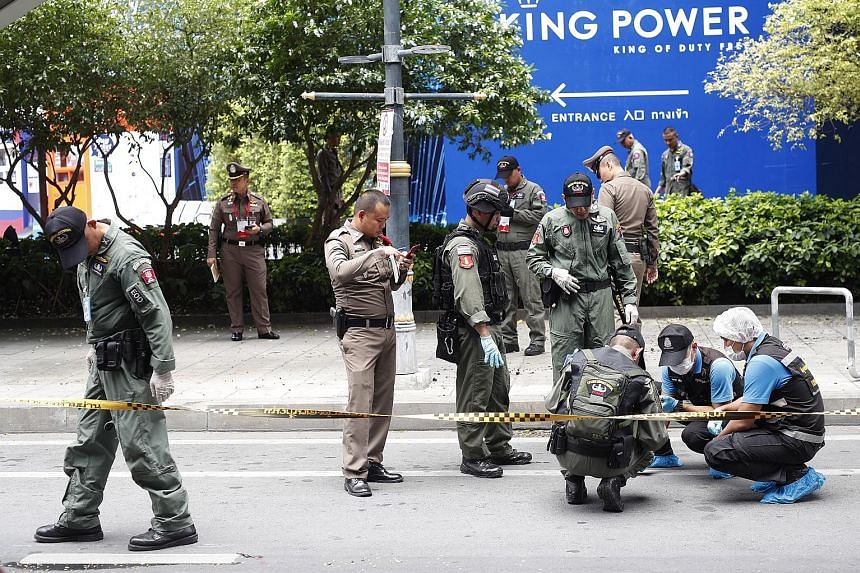 """Thai bomb squad members and forensic police officers inspecting the area where a small bomb exploded in Bangkok last Friday. """"We need to find the masterminds, but it's not easy,"""" said Police Lieutenant-General Suwat Chaengyotsuk."""