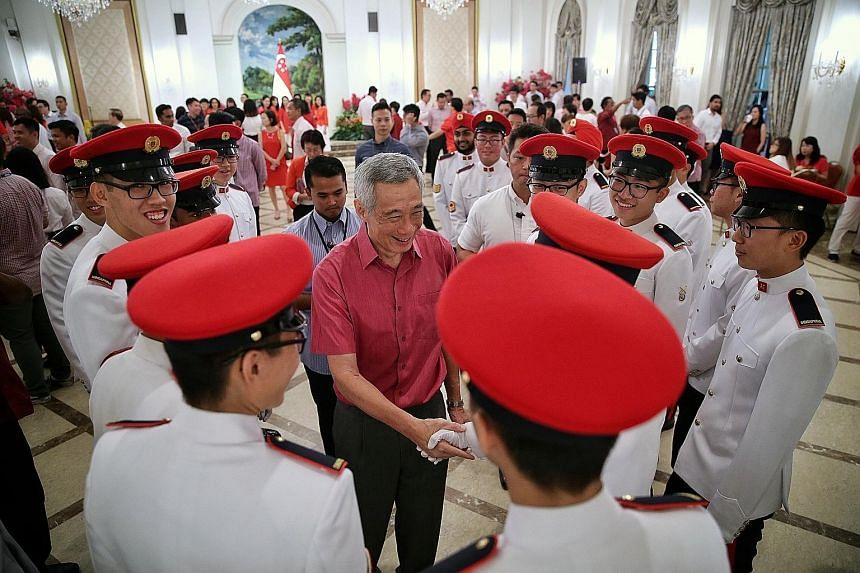 Prime Minister Lee Hsien Loong meeting Presidential Guards from the Military Police during the National Day Observance Ceremony at the Istana yesterday. ST PHOTO: KEVIN LIM
