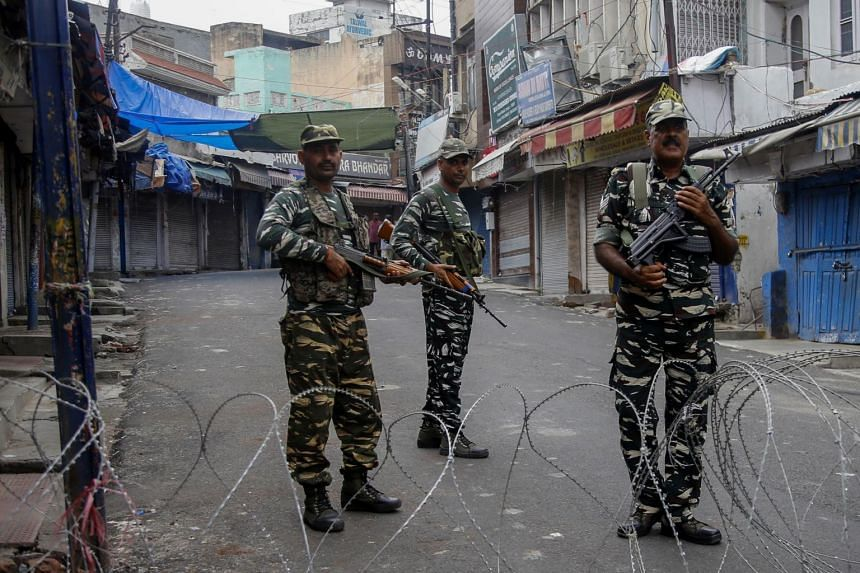 Security personnel standing guard at a roadblock ahead of the Friday prayers in Jammu, on Aug 9, 2019.