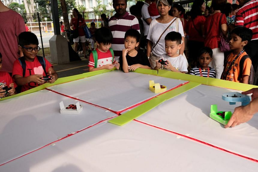 Children learning how to operate drones at one of the booths at the Moulmein-Cairnhill National Day observance ceremony on Aug 9, 2019.