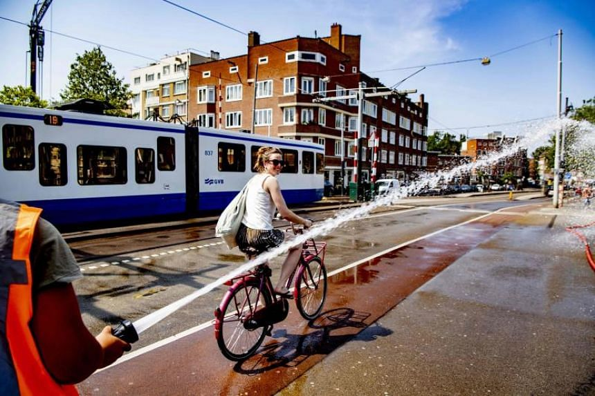 A woman rides her bicycle on the Wiegbrug bridge, during a heatwave in Amsterdam, on July 25, 2019.