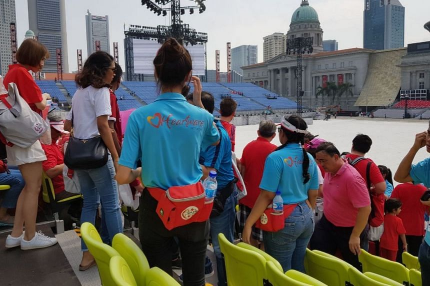 Early birds finding their seats at the Padang with the help of volunteers in blue.