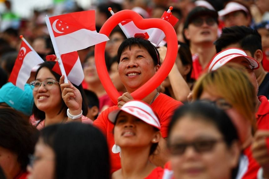 A spectator with a heart-shaped balloon waving Singapore's National Flag in the crowd at the Padang.