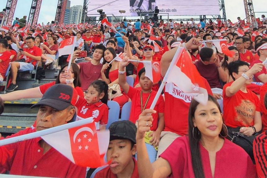 Spectators waving their flags as they join in the celebrations at the National Day Parade 2019 held at the Padang on Aug 9, 2019.