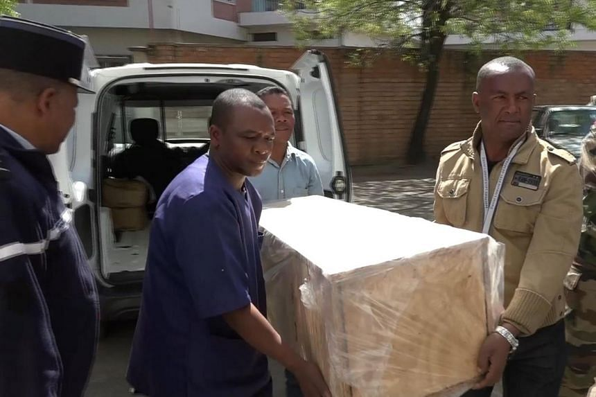 Hospital morgue employees carry a coffin containing the remains of Alana Cutland.
