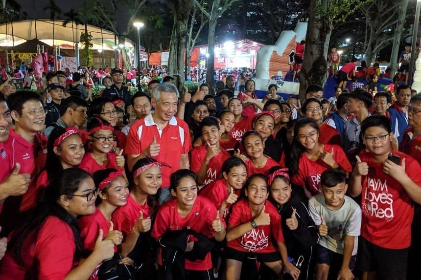 Prime Minister Lee Hsien Loong with student volunteers from North Vista Secondary and Northlight School at a Sengkang South grassroots National Day celebration on Aug 8, 2019.