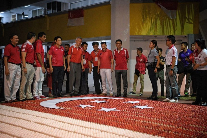 PM Lee looking at a giant flag of Singapore made with painted eggs at the Sengkang South community celebration, on Aug 8, 2019.