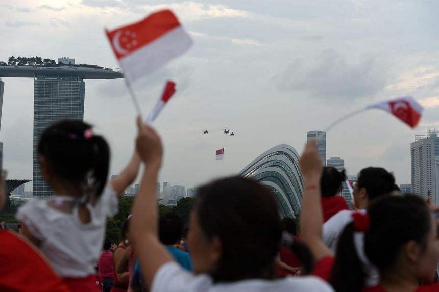 Republic of Singapore Air Force helicopters perform a fly over with the national flag during the 53rd National Day parade and celebration in Singapore on August 9, 2018.