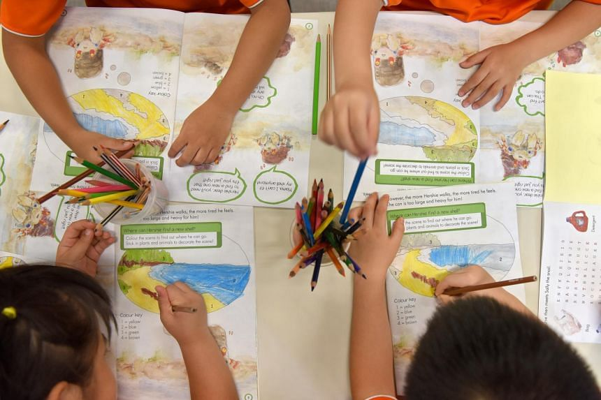 Pre-school students engaged in a colouring exercise.
