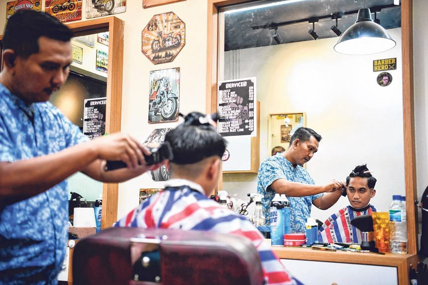 Below: Mr Tahir doing a fade haircut for a customer. A gradual blend of different lengths for the sides and back, it can take an hour to complete and involves tapering the hair from the crown to the neck to make the hairstyle look seamless. Mr Tahir