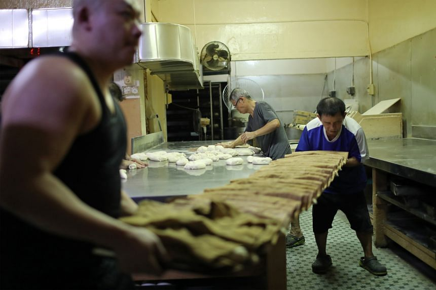 While Mr Tan kneads dough to make more loaves, Mr Wong Meng Huat (in blue) and Mr Zong Wei Dong transfer the shaped dough, covered and separated by brown cloth, for baking.