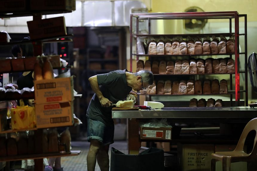 Mr Tan Hock Heng, a long-time employee of Sing Hon Loong Bakery, slicing freshly baked bread according to customers' preferred thickness. With most employees over 60 years old and no successor in mind, this family business at 4 Whampoa Drive, in Bale
