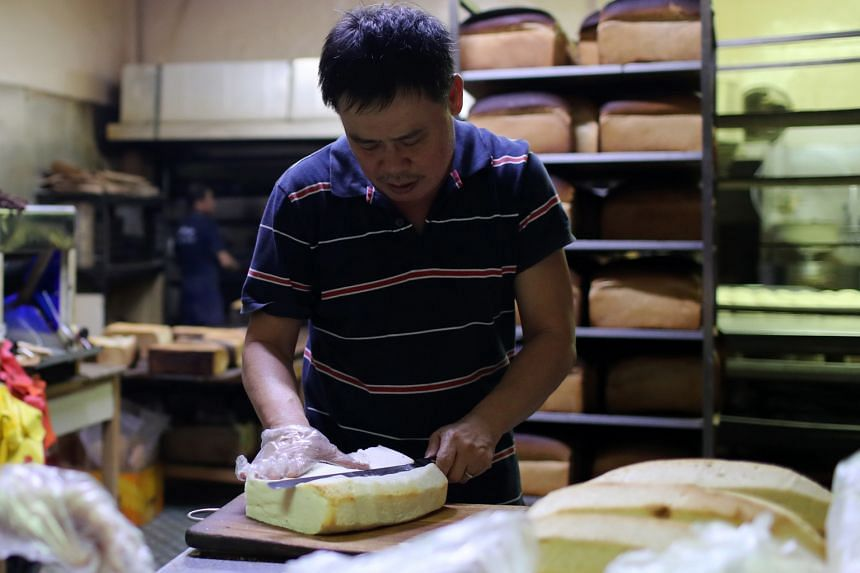 The baked bread is cooled on shelves before the crust is cut (above, here by bakery owner Lai Chee Peng) and binned. The loaf is sliced and then bagged.