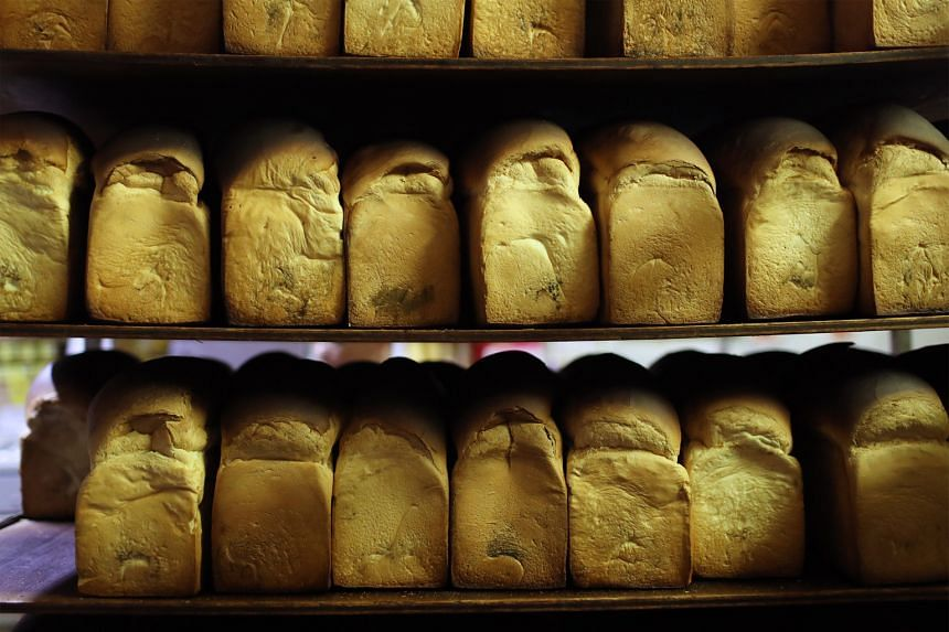 The baked bread is cooled on shelves (above) before the crust is cut.