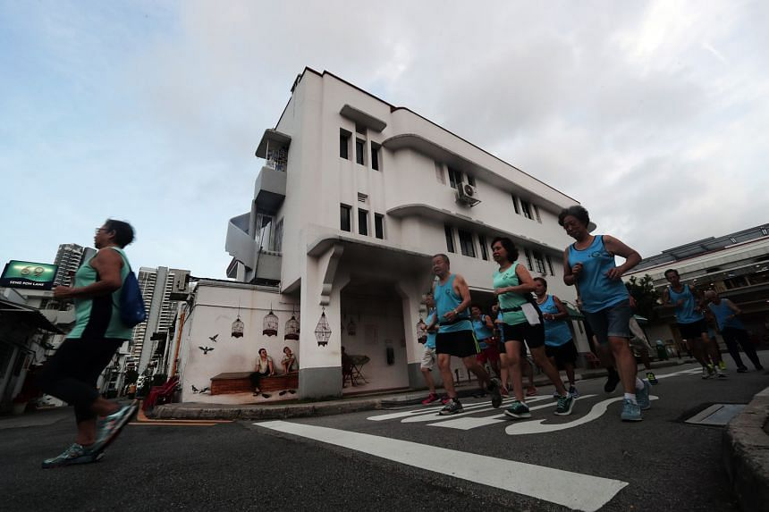 Members of the Tiong Bahru Garden Joggers club jogging past pre-war houses in Tiong Bahru. Every Sunday, the group meets to walk and jog through the more striking parts of the estate.
