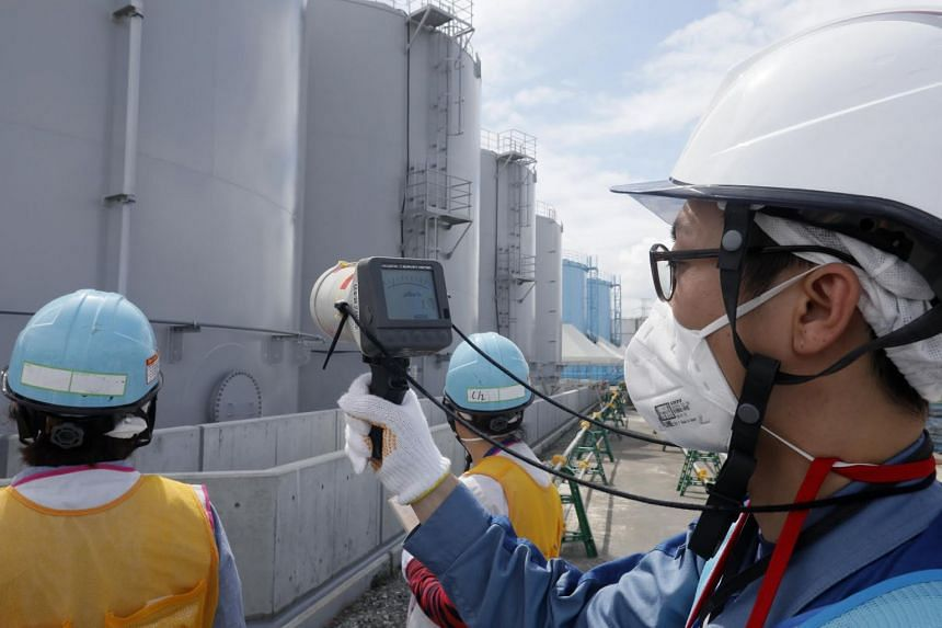 A 2018 photo shows a Tepco staff member measuring radiation levels around Fukushima water-storage tanks.