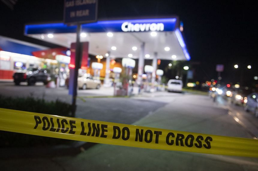 A warning tape secures the scene at a Chevron gas station, where a man stabbed multiple people.