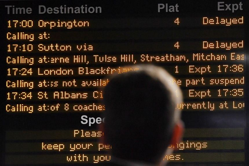 Commuters wait for delayed trains at a station in London.