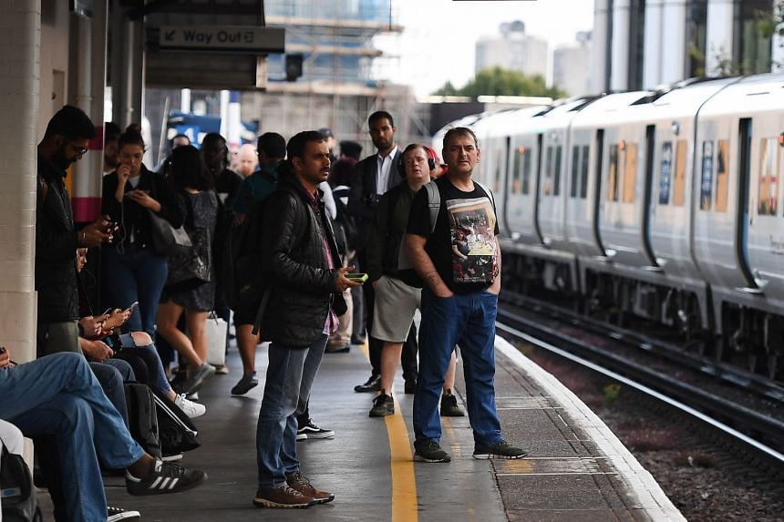 Commuters wait for delayed ThamesLink trains at Elephant and Castle station in London.