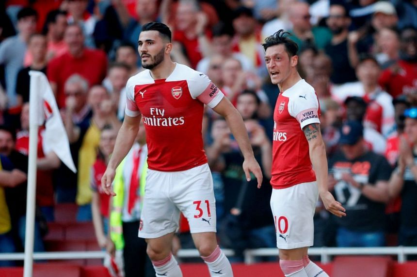Arsenal's Mesut Ozil celebrates a goal with Sead Kolasinac.