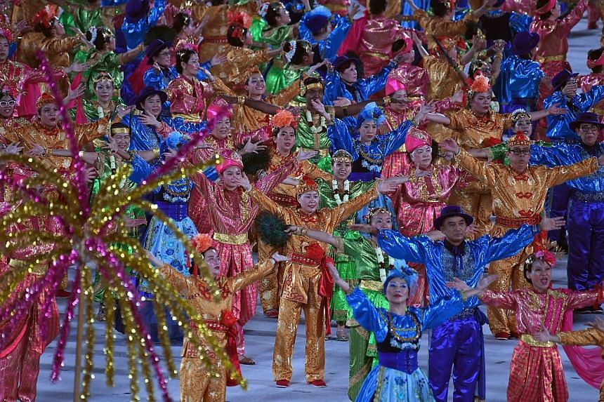 Dancers representing the four major races - Chinese (orange), Malay (green), Indian (pink) and Eurasian (cyan) - coming together in a multicultural dance segment by the People's Association.