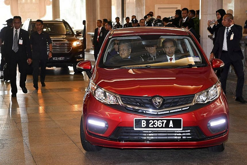 Malaysian Prime Minister Mahathir Mohamad driving visiting Indonesian President Joko Widodo in a Proton Persona from his office at the Perdana Putra Building to a luncheon at his official residence in Putrajaya yesterday. PHOTO: BERNAMA