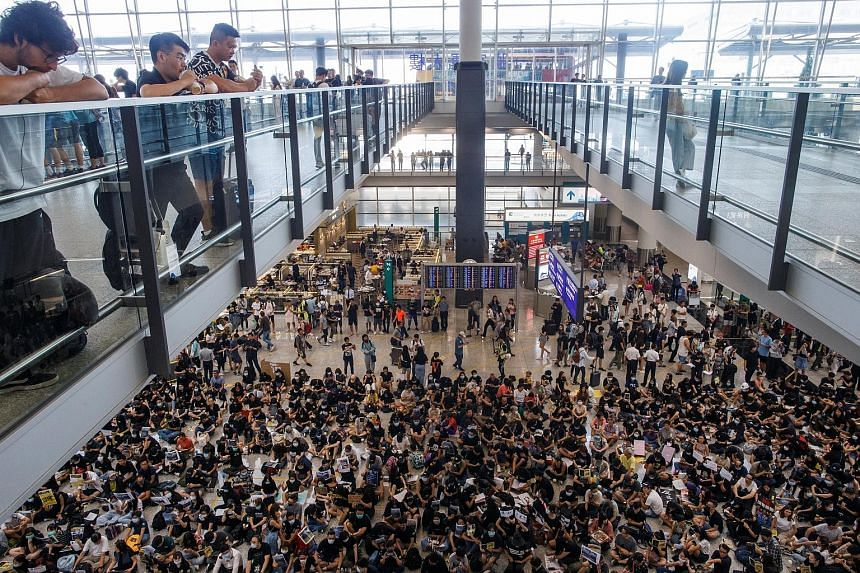 Above: People staging a sit-in at Hong Kong International Airport's arrival hall yesterday. Thousands of protesters gathered there to spread their message to arriving travellers, holding up placards (left) and handing out leaflets (below) in a bid to
