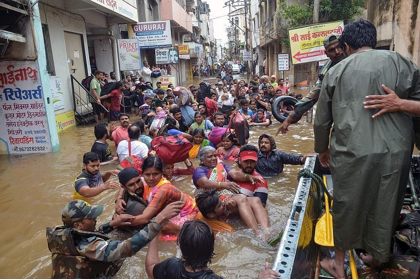 Indian Army personnel rescuing people on the outskirts of Sangli, Maharashtra state, on Thursday. At least 38 people have died in Maharashtra, Karnataka and Goa this week due to the monsoon rains. PHOTO: AGENCE FRANCE-PRESSE