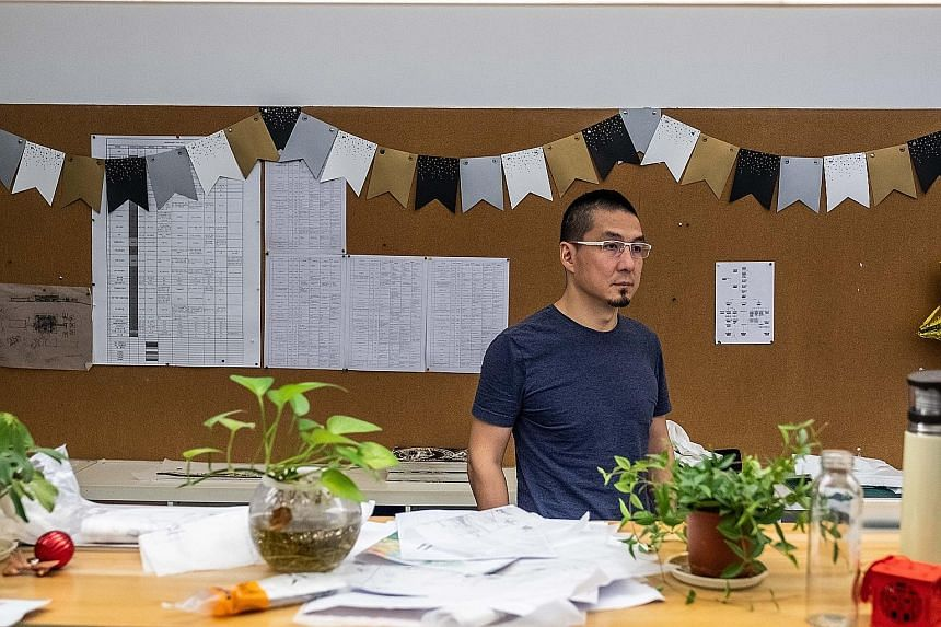 Mr Zhang Zhiyang at his architecture firm in Shenzhen. He is now accepting the financial equivalent of IOUs from as many as one-third of his clients instead of cash, with China's economy and his own business slowing. PHOTO: NYTIMES