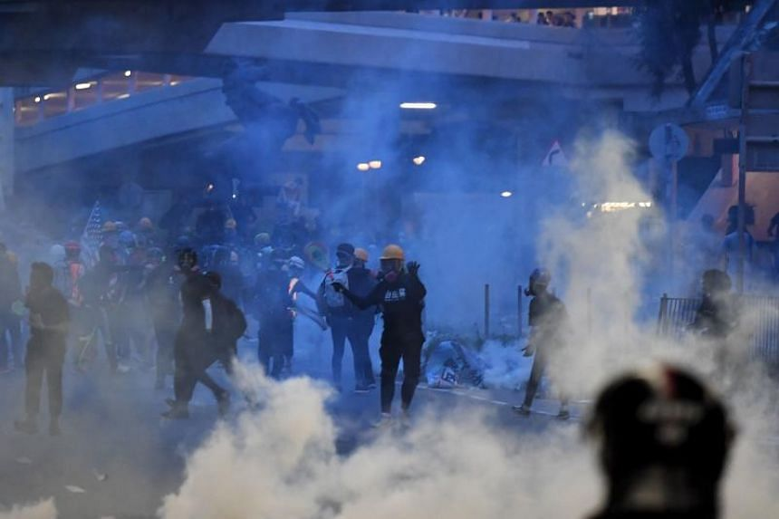 Protesters throwing tear gas canisters back at police in Tai Wai, Hong Kong, on Aug 10, 2019.