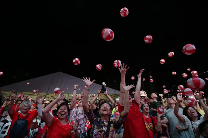 Participants throwing red and white paper balls into the air during the National Day Heartlands Celebration in Punggol, in an attempt to break a Singapore record, on Aug 10, 2019.