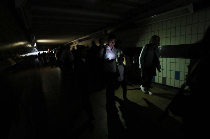 People walking in darkness at Clapham Junction station in London during a power cut on Aug 9, 2019.