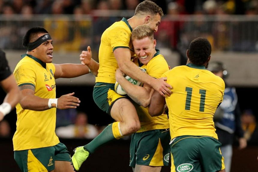 Reece Hodge (centre) of the Australian Wallabies is congratulated by teammates after scoring a try against the New Zealand All Blacks in their Bledisloe Cup match on Aug 10, 2019.