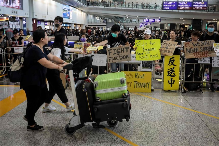 Protesters offering leaflets to travellers arriving at Hong Kong International Airport, on Aug 10, 2019.