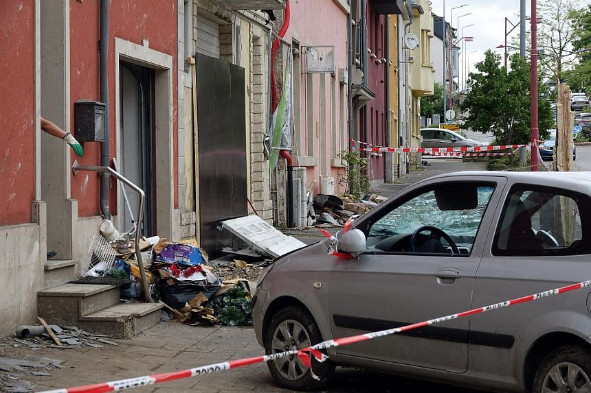 Debris and a damaged car are seen on a street in the town of Petange, Luxembourg, after a tornado hit the area, on Aug 10, 2019.