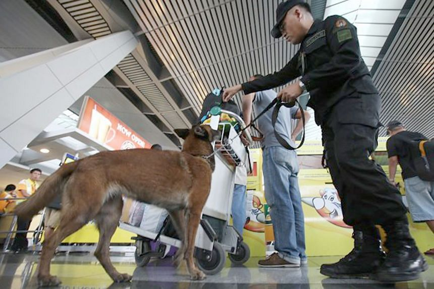A file photo of a security officer inspecting travellers at the Ninoy Aquino International Airport. Philippine security officials are investigating reports against two Sri Lankans who entered the country, even as one of them denied accusations agains