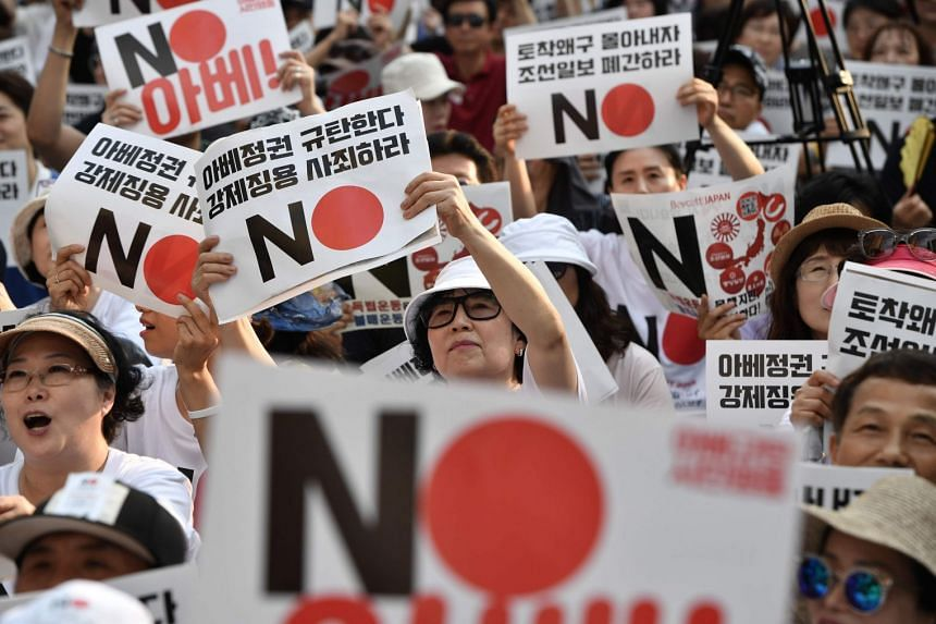 """Protesters hold up placards reading """"No (Japan)"""" during a rally against Japan's decision to remove South Korea from a so-called """"white list"""" of favoured export partners."""